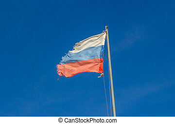 The flag of the Russian Federation damaged by a strong wind on a flagpole against a blue sky