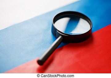 The flag of the Russian Federation looks through a magnifying glass. The study of the history and culture of the people of a large country of Russia. The concept of studying geography