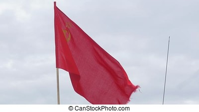 The flag of the USSR developing in the wind on a flagpole in...