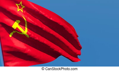 The flag of USSR flutters in the wind against a blue sky