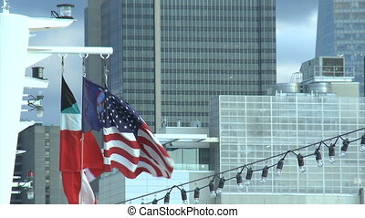 the flags fluttering on the ship,buildings in the background