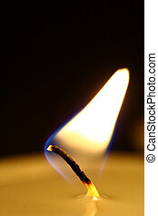 The flame of a candle burning down plays on a black