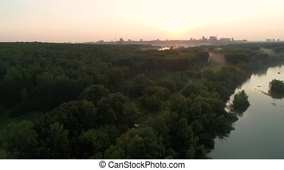 the flight of the drone over the river at sunset . beautiful little island