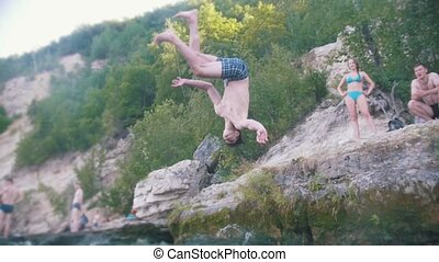 The flip jump in the river with a cliff on the nature, slow motion