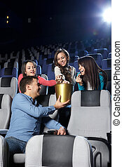 The flirting man - The young man at cinema gives girls...