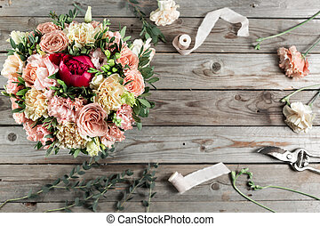 The florist desktop with working tools on gray old wooden background.
