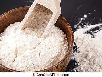 The flour in a wooden bowl and shovel on a black background