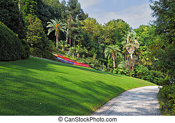 The flowerbeds, green grassy lawn and comfortable path in an exotic park. Lake Como, Villa Carlotta
