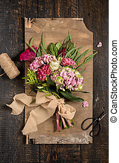 The different flowers on dark wooden background.