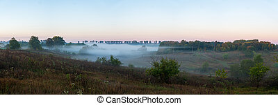 The fog over the river flows through the valley.