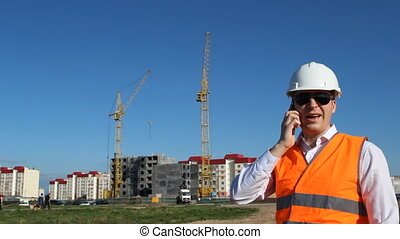 The foreman is talking on the phone on the background of the construction of an apartment house