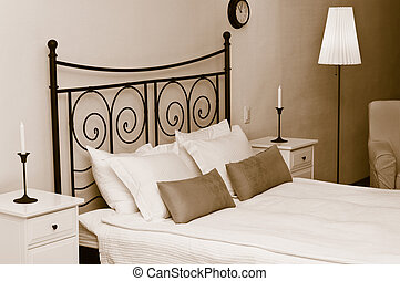 The forged headboard of bed with pillows and a white...