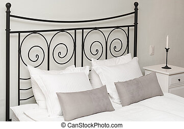 The forged headboard of bed with pillows and a white coverlet. Candles in a room interior, a bedroom