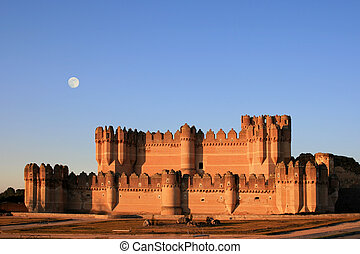 The fortress of Coca (Spain) at dusk with full moon - The...