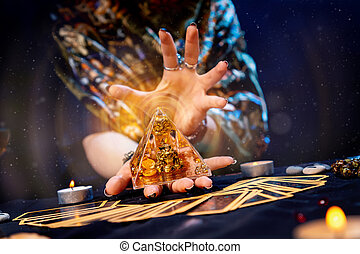 The fortune teller holds a glass pyramid with gold in her hands and casts a spell over it. Magic aura. There are Tarot cards on the table. Close-up. The concept of divination, magic and esotericism