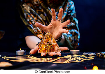The fortune teller holds a glass pyramid with gold in her hands and casts a spell over it. There are Tarot cards on the table. Close-up. The concept of divination, magic and esotericism