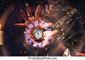 The fortune teller holds a watch on a chain in her hands and conjures over it. A luminous zodiac circle is depicted around the clock. The concept of divination, astrology and predicting the future