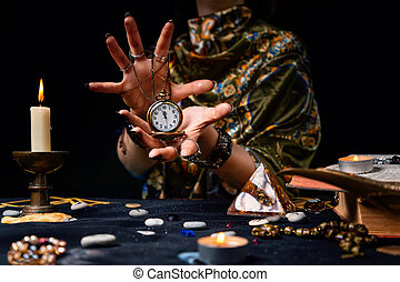 The fortune teller holds a watch on a chain in her hands and conjures over it. The concept of divination, astrology and predicting the future