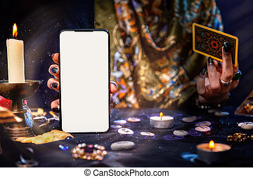 The fortune teller is holding a Tarot card and a smartphone with a white screen. Magic aura. Mock up. Close-up. The concept of divination, magic and esotericism