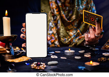 The fortune teller is holding a Tarot card and a smartphone with a white screen. Mock up. Close-up. The concept of divination, magic and esotericism