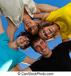 The four friends, embracing, has formed a circle and bent over a photographer