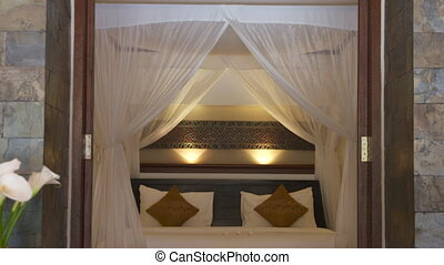 A closeup shot with a downward tilting view of the four-post queen-size bed draped in white muslin curtain with an upholstered wooden bench in front inside the bedroom of a luxurious hotel..