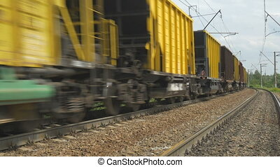 The freight train goes on rails. The view of the last car that leaves in the distance.