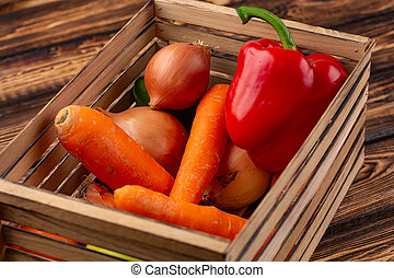 the Fresh multi-colored vegetables in wooden crate.