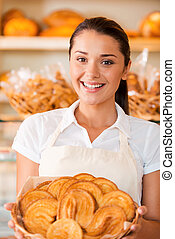 The freshest bakery for our customers. Beautiful young woman in apron holding basket with baked goods while standing in bakery shop