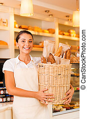 The freshest bread for our customers. Beautiful young woman in apron holding basket with bread and smiling while standing in bakery shop