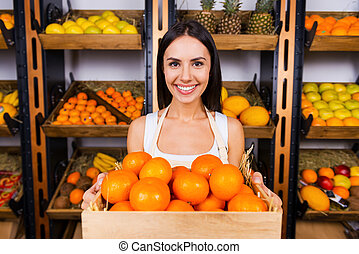 The freshest tangerines for you. Beautiful young woman in apron holding wooden container with tangerines and smiling while standing in grocery store with variety of fruits in the background