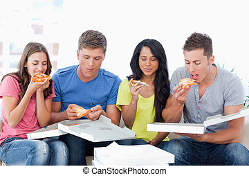 The friends tuck into the pizza just bought