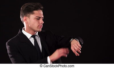 The frowning guy points at the wristwatch on his wrist