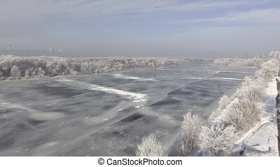 The frozen river in the forest in winter, the snow on the trees, the view from the air