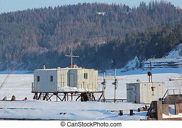 The frozen river port. Cranes, barges, old buildings.