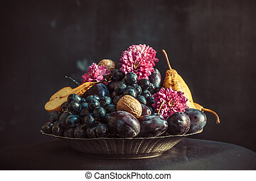 The fruit bowl with grapes and plums against a dark wall