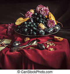 The fruit bowl with grapes and plums against a maroon tablecloth