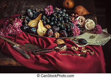 Fruit bowl with grapes and plums against a maroon tablecloth