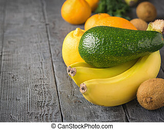 The fruit is green, ripe avocado, three bananas and other tropical fruits on a rustic table.