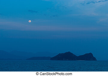 The full moon shining over the sea and the island.