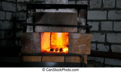 The furnace of a blacksmith engulfed in flames, in the forge