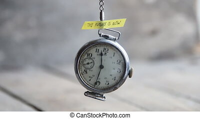 the future is now text and pocket watch hang on chain gray background