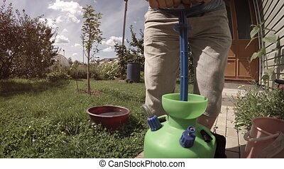 The gardener presses the apparatus for spraying plants with pesticides