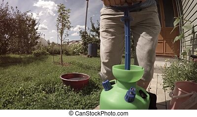 The gardener presses the apparatus for spraying plants with pesticides. UltraHD 4k footage with sounds