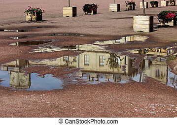 The Gatchina Palace is reflected in a puddle on the parade ground after a rain.