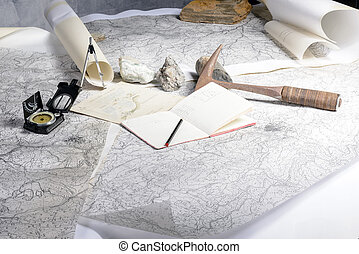 The geological expedition is prepared with the study of topographic maps. On the table the tools of the geologist.