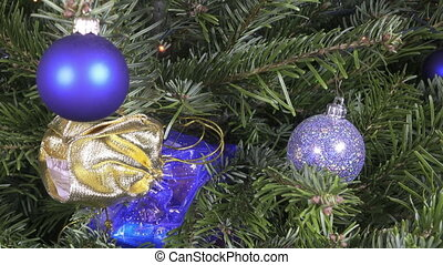 The gift bag is hidden on branches of a New Year tree,