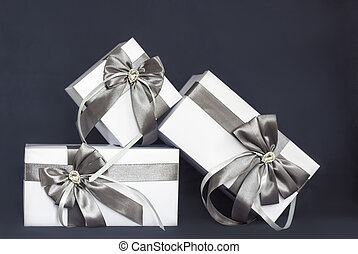 The gift box is white with a beautiful gray bow. Gift on a dark background.