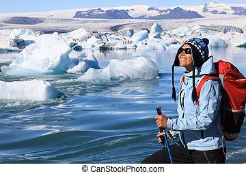 The girl admires the beauty of the glacial lagoon Jokulsarlon