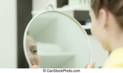 The girl after a hair-cutting looks at itself in a mirror
